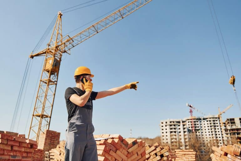 Worker giving instructions to crane with mobile phone like in the case study with ViiBE and Bouygues Construction