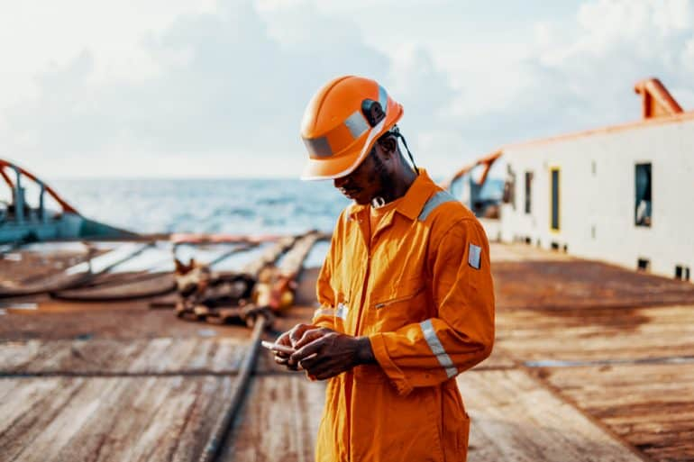 Worker benefiting from offshore connectivity to use cell phone