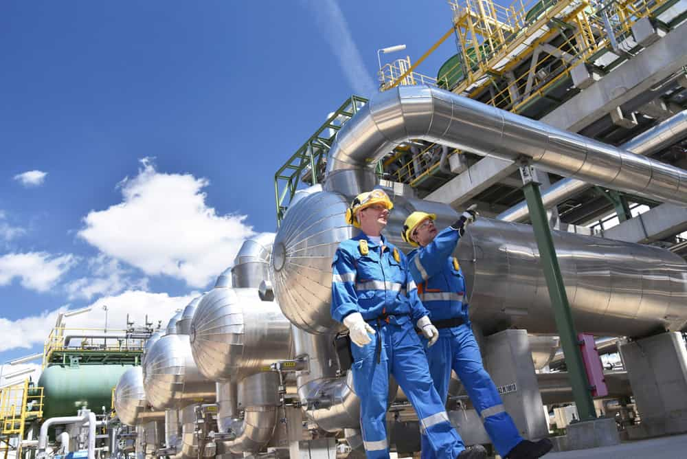 Two workers at a refinery, working downstream in the oil and gas value chain